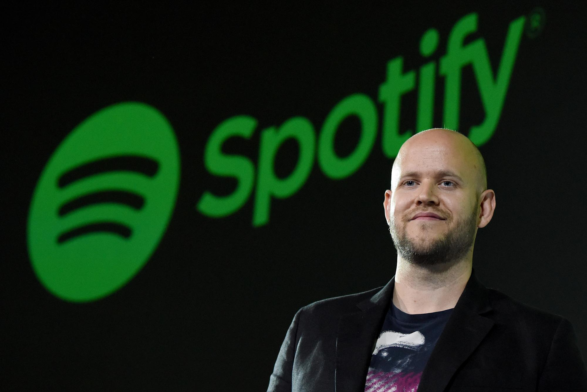 Spotify CEO standing in front of Spotify logo